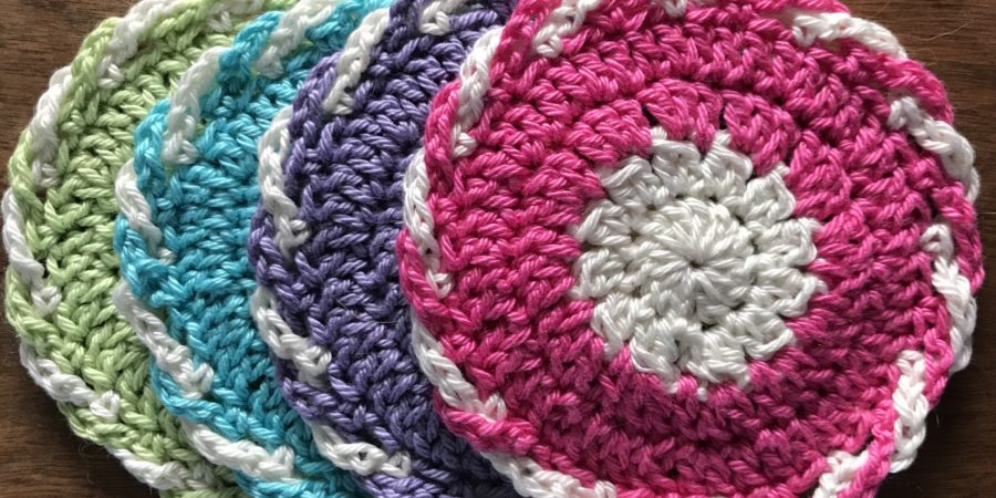 four crocheted coasters in green, blue, purple and pink